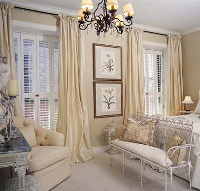 White shutter panels with creamy curtains create a bedroom escape.